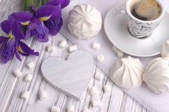 与杯子的静物画coffe蛋白软糖过眼云烟的虹膜开花在白色木背景的心脏标志 免版税库存图片