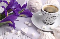 与杯子的静物画coffe蛋白软糖过眼云烟的虹膜开花在白色木背景的心脏标志 免版税库存照片