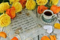 与杯子的黄色玫瑰红茶、心脏装饰、珍珠项链和音乐纸张 免版税库存图片