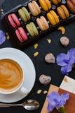 与杯子的Makarons您喜爱的咖啡、书和蓝色花在黑石背景 免版税库存图片