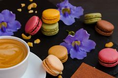 与杯子的Makarons您喜爱的咖啡和蓝色花在黑石背景 它` s真正地惊人的早晨 免版税库存图片