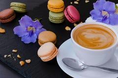 与杯子的Makarons您喜爱的咖啡和蓝色花在黑石背景 库存图片