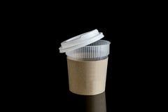 与杯座的被开张的外卖咖啡 隔绝在黑backgr 库存图片
