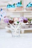 与杯形蛋糕点心桌的棒棒糖在结婚宴会 图库摄影
