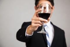 与杯的亚洲商人在玻璃的红葡萄酒焦点 图库摄影
