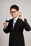 与杯的亚洲商人展示OK红葡萄酒 免版税图库摄影
