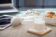 与杯的办公室桌牛奶、点心和办公用品 库存图片