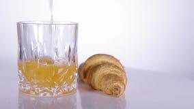 与杯的新月形面包在白色转动的桌上的汁液 股票视频