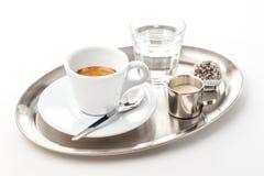 与杯的浓咖啡与奶油和蛋糕的水在金属片,隔绝在白色背景,咖啡产品摄影  免版税库存图片