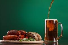 与杯的烤香肠啤酒 免版税库存照片