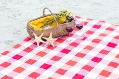 与杯的野餐篮子红葡萄酒和海星在毯子 免版税库存图片
