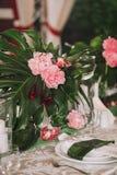 与板材的一张美丽的服务的桌用orchi的棕榈树、白色蜡烛和花的叶子装饰的晚餐会的 图库摄影