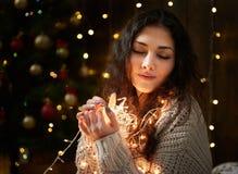 与极少数的梦中情人画象圣诞灯,闭合的眼睛,穿戴在白色毛线衣,黑暗的木背景,冬天hol 免版税库存照片