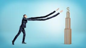与极端设法长的胳膊的一个商人捉住与一个金黄美元的符号的一个小企业大厦在上面 免版税图库摄影
