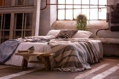 与枕头和毯子的床,板凳和植物在wabi sabi卧室 免版税库存照片