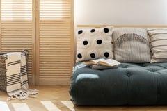 与枕头的斯堪的纳维亚蒲团在现代公寓宽敞客厅内部  库存照片