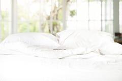 与枕头和毯子的杂乱白色床在混凝土墙backgro 免版税库存照片