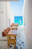 与枕头的长凳在一个典型的希腊室外咖啡馆在米科诺斯岛有在基克拉泽斯海岛上的惊人的海视图 库存照片