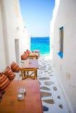 与枕头的长凳在一个典型的希腊酒吧在米科诺斯岛有在基克拉泽斯海岛上的惊人的海视图 免版税库存照片