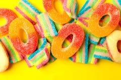 与果冻和糖的糖果 五颜六色的一些不同的childs甜点和款待 明亮的党背景 免版税图库摄影
