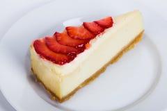 与果冻和草莓切片的乳酪蛋糕在菜单的一个板材特写镜头 图库摄影
