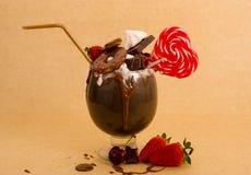 与果仁巧克力蛋糕,草莓,樱桃,与心脏形式,塑料秸杆的糖果的巧克力纵容极端奶昔 免版税库存照片