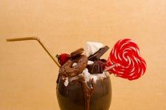 与果仁巧克力蛋糕,草莓,樱桃,与心脏形式,塑料秸杆的糖果的巧克力纵容极端奶昔 库存照片