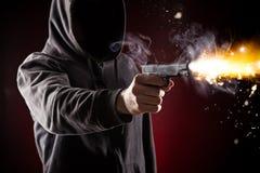 凶手_与枪关闭的一个凶手在难看的东西背景.