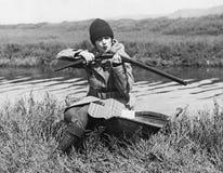 与枪的女性猎人在河附近(所有人被描述不更长生存,并且庄园不存在 供应商保单ther 免版税库存照片