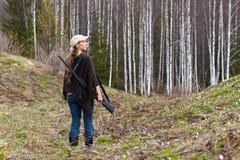 与枪的妇女猎人在森林里 库存照片