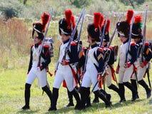 与枪的战士行军。 免版税库存照片