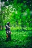 与枪的男性猎人在多雨天气走在春天森林 库存照片