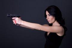 与枪的年轻性感的妇女射击在灰色 免版税库存图片