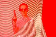 与枪的间谍代理在红色和黄灯绘画背景 库存照片