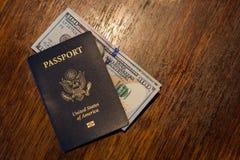 与某一美元的蓝色美国护照在一张木书桌顶部 库存图片
