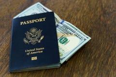 与某一美元的蓝色美国护照在一张木书桌顶部 免版税库存照片