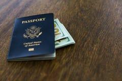 与某一美元的蓝色美国护照在一张木书桌顶部 库存照片