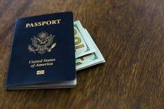 与某一美元的蓝色美国护照在一张木书桌顶部 图库摄影