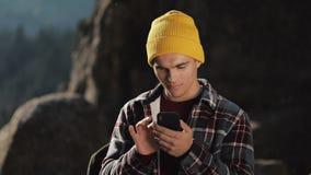 与某人的年轻愉快的人闲谈他的在岩石的上面的电话身分的在美丽的山前的 通信 影视素材