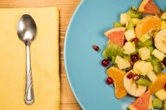 与柑橘在与一个餐巾、匙子和地方的一张木桌上站立题字的一块蓝色板材, co的新鲜水果沙拉 库存照片