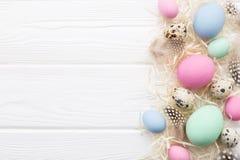 与柔和的淡色彩的复活节框架上色了在白色木桌上的鸡蛋 库存照片