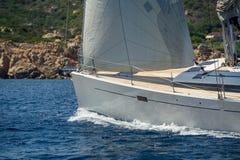 与柚木树甲板的豪华新的巡航的风船弓在被卷扬的风帆下 库存图片