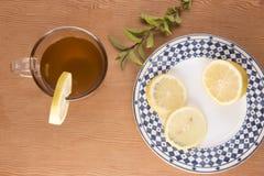 与柠檬切片和绿色叶子的柴茶 免版税图库摄影