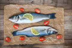 与柠檬切片的两条未加工的雪鱼鱼和在w的西红柿 库存图片