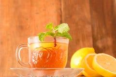 与柠檬切片的柠檬茶杯和在木背景的薄荷的叶子 图库摄影