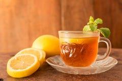 与柠檬切片的柠檬茶杯和在木背景的薄荷的叶子 库存照片