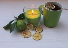 与柠檬切片的茶与叶子和蜡烛的干和新鲜的柠檬 免版税库存照片
