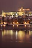 与查理大桥的夜浪漫五颜六色的多雪的布拉格哥特式城堡 免版税库存图片