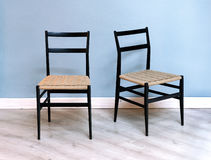 与柳条位子的两把简单的黑椅子 免版税库存照片