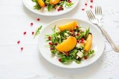 与柿子、芝麻菜、乳酪和石榴种子的新鲜的秋天沙拉在白色桌布 免版税库存照片